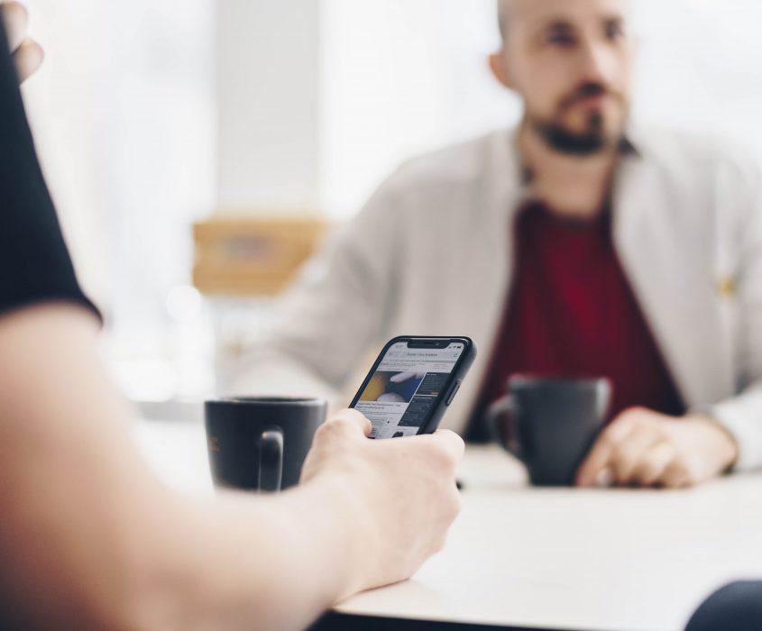 Personer som håller mobiltelefon och dricker kaffe med en kollega