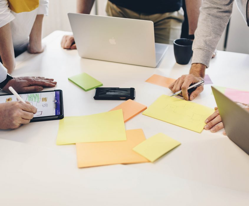 Bord med Ipad, posits, datorer och människor som samtalar
